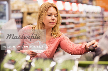 Woman buying groceries in supermarket Stock Photo - Premium Royalty-Free, Image code: 698-07635215