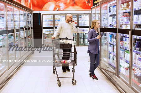 Full length of father and daughter buying groceries in supermarket Stock Photo - Premium Royalty-Free, Image code: 698-07635222