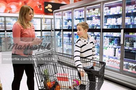 Mother and son with shopping cart in grocery store Stock Photo - Premium Royalty-Free, Image code: 698-07635224