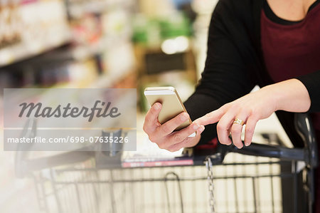 Midsection of woman checking shopping list in supermarket Stock Photo - Premium Royalty-Free, Image code: 698-07635226