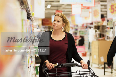 Mid adult woman buying groceries in supermarket Stock Photo - Premium Royalty-Free, Image code: 698-07635227