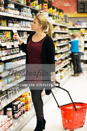 Mid adult woman shopping groceries with children in background at supermarket Stock Photo - Premium Royalty-Free, Image code: 698-07635229