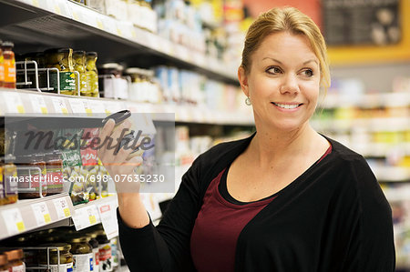 Smiling woman looking away while buying groceries in supermarket Stock Photo - Premium Royalty-Free, Image code: 698-07635230