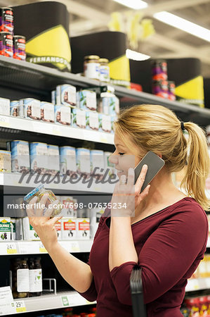 Mid adult woman answering smart phone while buying groceries in supermarket Stock Photo - Premium Royalty-Free, Image code: 698-07635234