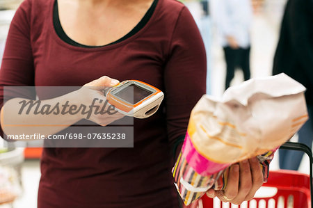 Midsection of woman scanning product with bar code reader in supermarket Stock Photo - Premium Royalty-Free, Image code: 698-07635238