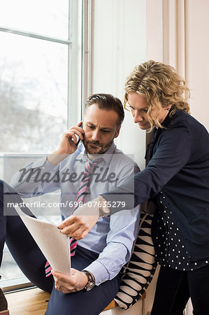 Businessman answering smart phone while discussing over document with female colleague by office window Stock Photo - Premium Royalty-Free, Image code: 698-07635279