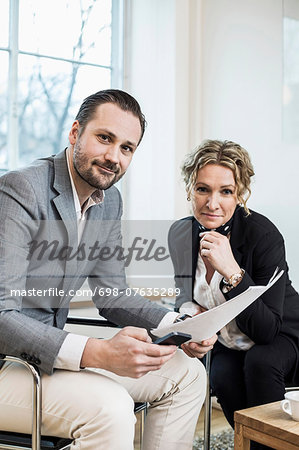 Portrait of confident business people with paperwork in office Stock Photo - Premium Royalty-Free, Image code: 698-07635289