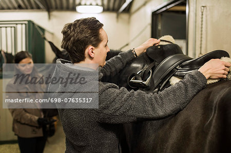 Young man preparing horse in stable with woman in background Stock Photo - Premium Royalty-Free, Image code: 698-07635317