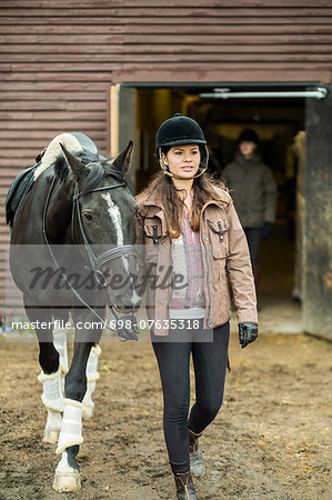 Young woman with horse walking outside barn with man in background Stock Photo - Premium Royalty-Free, Image code: 698-07635318