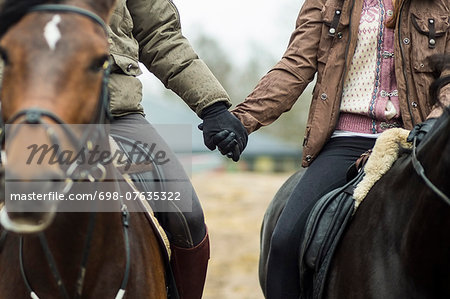 Low section of couple holding hands while riding horses Stock Photo - Premium Royalty-Free, Image code: 698-07635322