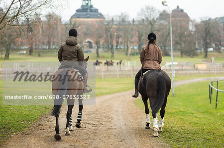 Full length rear view of young couple riding horses on dirt road Stock Photo - Premium Royalty-Free, Image code: 698-07635323