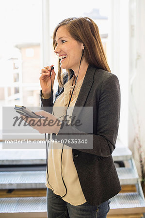 Smiling businesswoman listening to music through mobile phone in office Stock Photo - Premium Royalty-Free, Image code: 698-07635340
