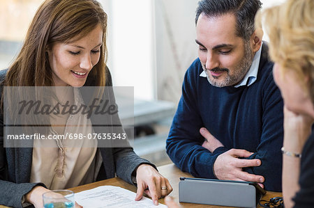 Multi-ethnic businesspeople discussing over document at desk in office Stock Photo - Premium Royalty-Free, Image code: 698-07635343