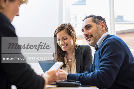 Businesspeople in meeting at office desk Stock Photo - Premium Royalty-Free, Image code: 698-07635345