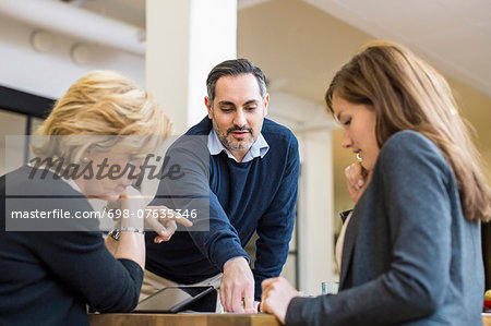 Businessman planning strategy with female colleagues at desk in office meeting Stock Photo - Premium Royalty-Free, Image code: 698-07635346