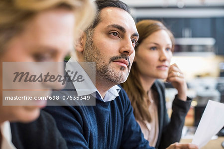Concentrated businessman looking away in office meeting Stock Photo - Premium Royalty-Free, Image code: 698-07635349