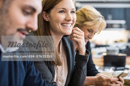 Smiling businesswoman looking away in office meeting Stock Photo - Premium Royalty-Free, Image code: 698-07635350