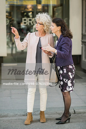 Full length senior women searching direction on digital tablet at city street Stock Photo - Premium Royalty-Free, Image code: 698-07635395
