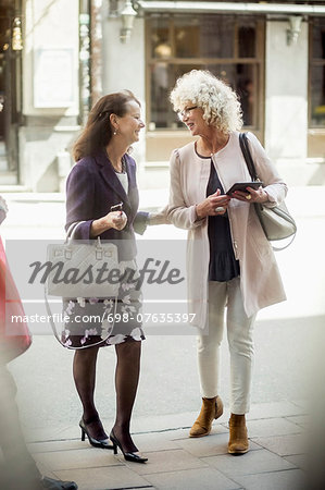 Happy senior female friends talking while walking on street Stock Photo - Premium Royalty-Free, Image code: 698-07635397