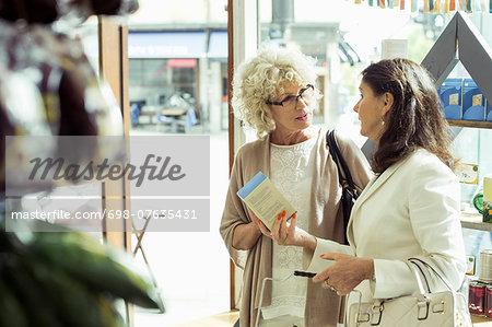 Senior women discussing over product in store Stock Photo - Premium Royalty-Free, Image code: 698-07635431