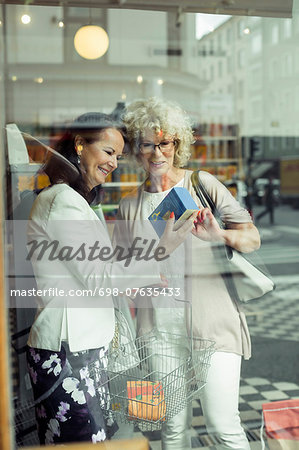 Smiling senior women reading instructions on product in store Stock Photo - Premium Royalty-Free, Image code: 698-07635433