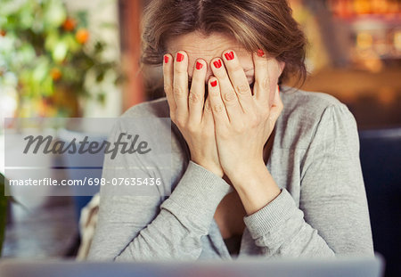 Sad young woman sitting with head in hands at home Stock Photo - Premium Royalty-Free, Image code: 698-07635436