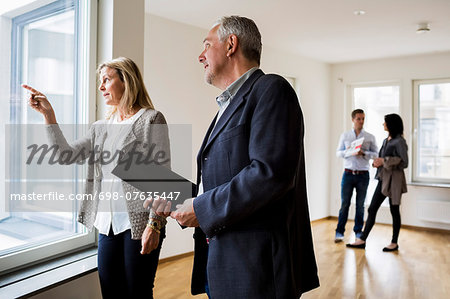 Real estate agents discussing while couple standing in background at new home Stock Photo - Premium Royalty-Free, Image code: 698-07635447