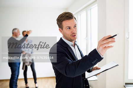 Real estate agent examining house with couple discussing in background Stock Photo - Premium Royalty-Free, Image code: 698-07635454