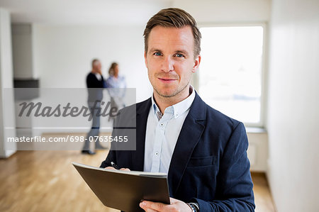 Portrait of confident real estate agent with couple standing in background at home Stock Photo - Premium Royalty-Free, Image code: 698-07635455