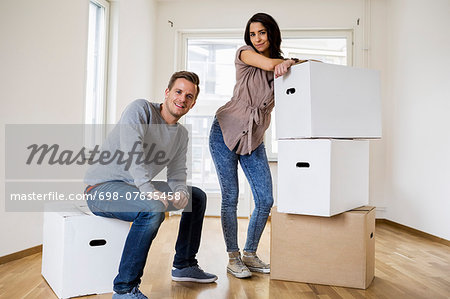 Full length of happy couple with moving boxes at home Stock Photo - Premium Royalty-Free, Image code: 698-07635458