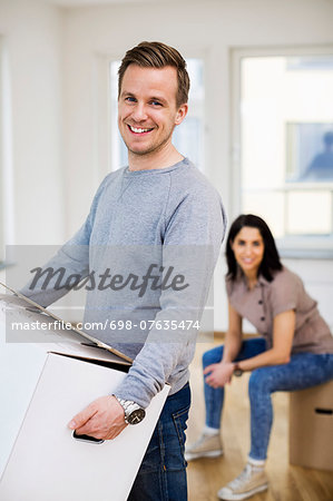 Portrait of happy man carrying cardboard box with woman in background at home Stock Photo - Premium Royalty-Free, Image code: 698-07635474