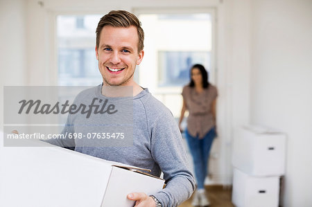 Portrait of happy man carrying moving box with woman in background at home Stock Photo - Premium Royalty-Free, Image code: 698-07635475