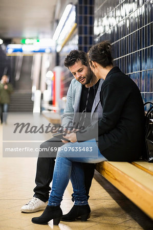 Full length of business people talking at subway station Stock Photo - Premium Royalty-Free, Image code: 698-07635483
