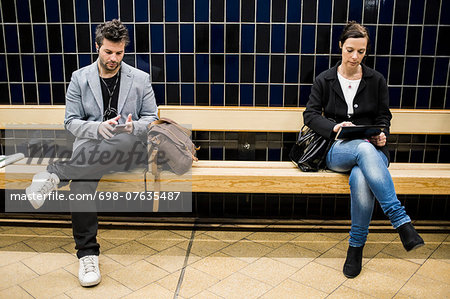 Full length of people using technologies on bench at subway station Stock Photo - Premium Royalty-Free, Image code: 698-07635487