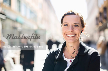 Portrait of smiling mature businesswoman listening to music on city street Stock Photo - Premium Royalty-Free, Image code: 698-07635489