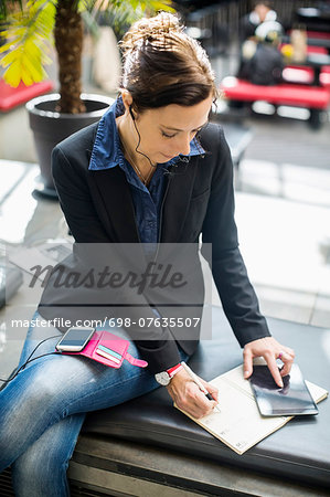 Mature businesswoman using digital tablet while writing in book at cafe Stock Photo - Premium Royalty-Free, Image code: 698-07635507