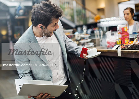 Panic mid adult man holding laptop and coffee at cafe Stock Photo - Premium Royalty-Free, Image code: 698-07635516