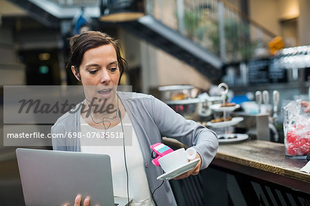 Panic mature woman holding laptop and coffee at cafe Stock Photo - Premium Royalty-Free, Image code: 698-07635518
