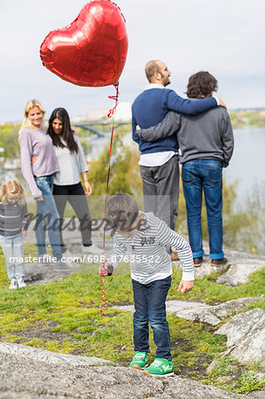 Boy holding balloon on rock with homosexual families in background Stock Photo - Premium Royalty-Free, Image code: 698-07635522