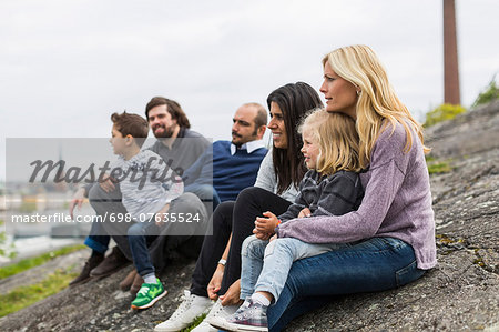 Homosexual families relaxing on rock at lakeshore Stock Photo - Premium Royalty-Free, Image code: 698-07635524