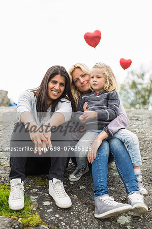 Portrait of happy female homosexual family relaxing on rock Stock Photo - Premium Royalty-Free, Image code: 698-07635525