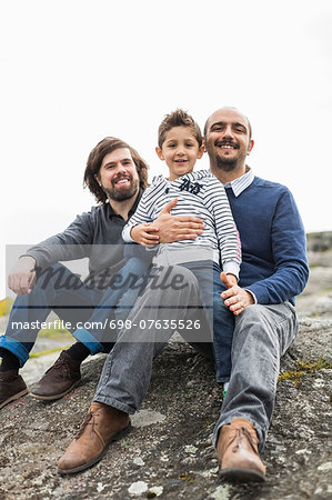 Portrait of happy male homosexual family relaxing on rock Stock Photo - Premium Royalty-Free, Image code: 698-07635526