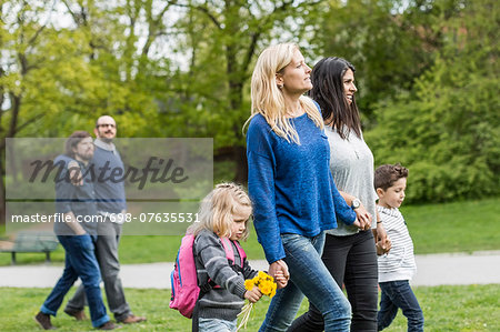 Female homosexual family walking at park with gay couple in background Stock Photo - Premium Royalty-Free, Image code: 698-07635531