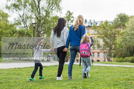 Rear view of female homosexual family walking in park Stock Photo - Premium Royalty-Free, Image code: 698-07635532