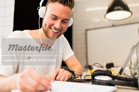 Happy young businessman wearing headphones while writing in book at creative office Stock Photo - Premium Royalty-Free, Image code: 698-07635558