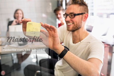 Young businessman sticking adhesive note on transparent glass with colleagues at background in new office Stock Photo - Premium Royalty-Free, Image code: 698-07635577