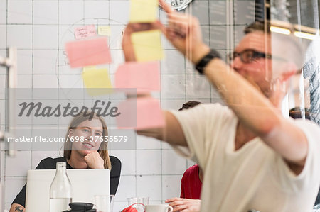 Young businessman writing ideas on adhesive notes with colleagues in background at creative office Stock Photo - Premium Royalty-Free, Image code: 698-07635579