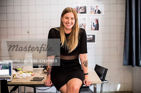 Portrait of smiling young businesswoman leaning at table in new office Stock Photo - Premium Royalty-Free, Image code: 698-07635603