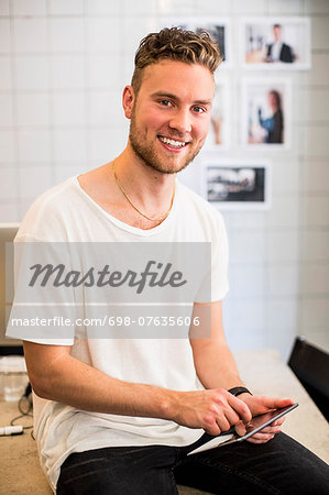 Portrait of happy young businessman using digital tablet in new office Stock Photo - Premium Royalty-Free, Image code: 698-07635606