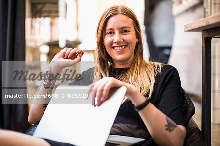 Portrait of happy young businesswoman with laptop sitting on bean bag in small office Stock Photo - Premium Royalty-Free, Image code: 698-07635619